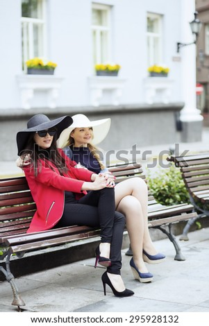 Two young females in different color hats - stock photo