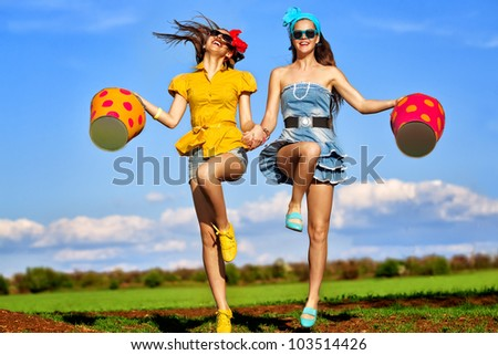 Two young females jumping with  buckets on garden - stock photo