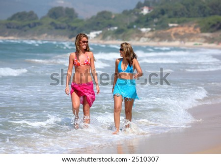 Two young, fit, beautiful tanned women walking along sunny, sandy beach whilst on vacation or holiday