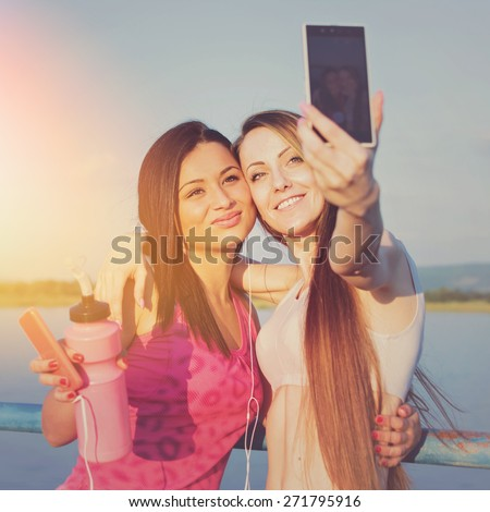 Two young fitness girls taking a selfie at the beach. Two girlfriends photographing themselves with smartphone after jogging outdoors on sunny summer day. Square format, retouched, filter applied. - stock photo