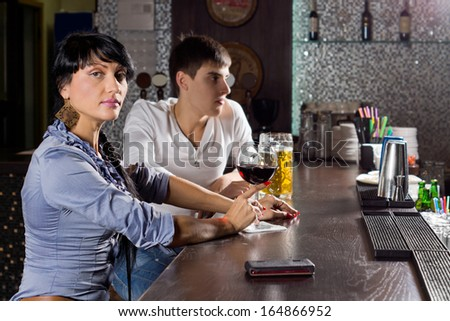Two young friends drinking together at the pub sitting at the bar counter with the woman turning to eye the camera with a serious assessing look - stock photo