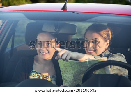Two young friends in car enjoy road trip. Travel concept.