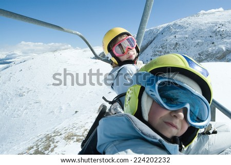 Two young friends on ski lift, both wearing ski goggles, one looking at camera
