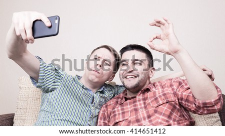 Two young funny guys taking selfie on smart phone sitting on sofa - stock photo