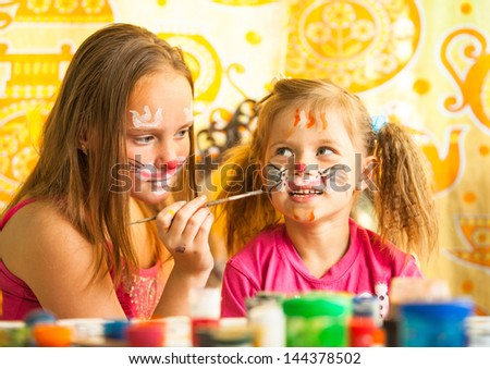 Two young funny sisters playing with painting - stock photo