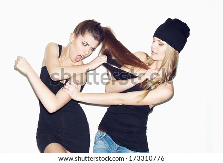 Two young girl friends having a quarrel. One keeping brunette's hair. Second pulling blonder's wear. Casual style. Inside - stock photo