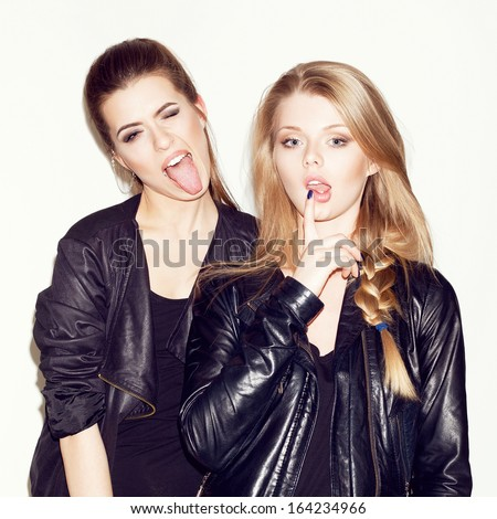 Two young girl friends having fun together (playing the ape). Brunette showing tongue. Blonde keeping her lips with finger. Inside - stock photo