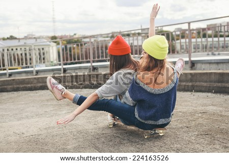 Two young  girl friends sitting together on longboard and having fun. Downhill, longboarding . Outdoors, lifestyle. - stock photo