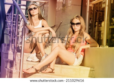 Two young girl friends sitting together outdoor - stock photo