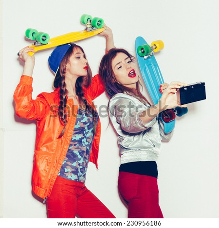 Two young girl friends standing having fun together.  Beautiful women making selfie. Emotion.  Hairstyle. Makeup.  White background, not isolated - stock photo