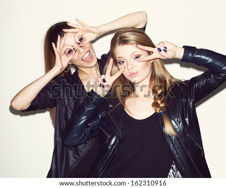 Two young girl friends standing together and having fun. Showing signs with hands. Looking at camera. Inside - stock photo