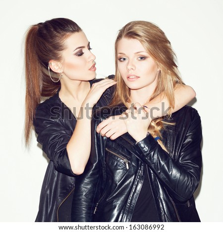 Two young girl friends standing together. Brunette put her hands on the blonde's shoulders. Inside - stock photo