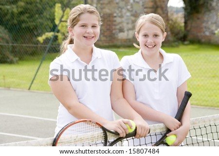 Two young girl friends with rackets on tennis court smiling - stock photo