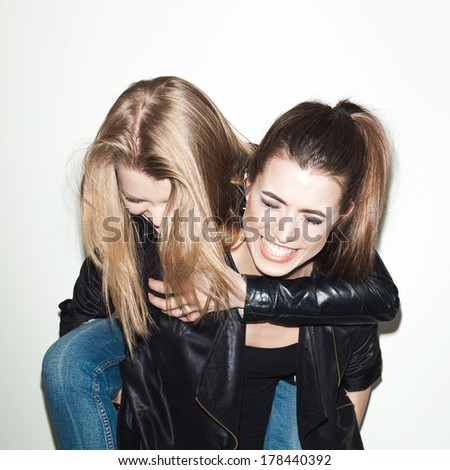 Two young girl hipster friends standing together, having fun.  indoor - stock photo