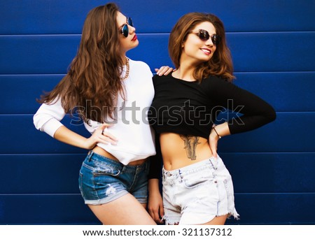 Two young girlfriends in sunglasses having fun. Lifestyle. - stock photo