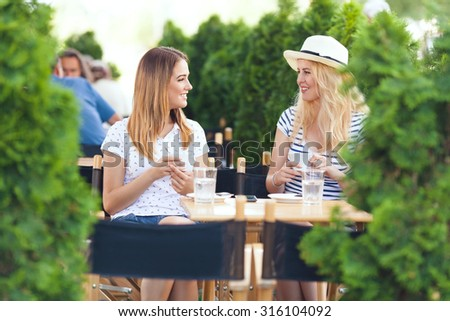 Two young girlfriends sitting in a cafe drinking coffee and chatting - stock photo