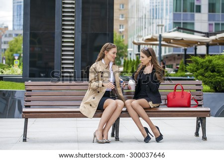 Two young girlfriends sitting on a bench in the town center  - stock photo