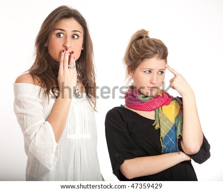 Two young girls, a blonde and a brunette, with a shocked expression - stock photo