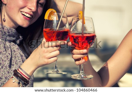 Two Young Girls and a Red Cocktail - stock photo