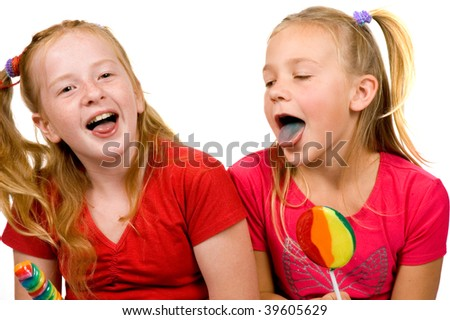 two young girls are showing their blue tongue after licking lolly-pop on white - stock photo