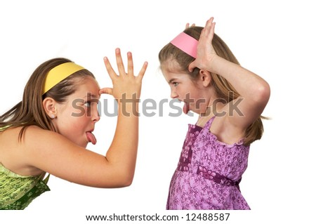 Two young girls fighting and sticking their tongues out at each other