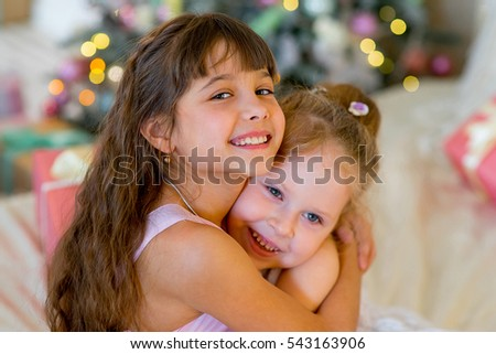 Two young girls give each other gifts in dresses on the bed hugs between Christmas gifts
