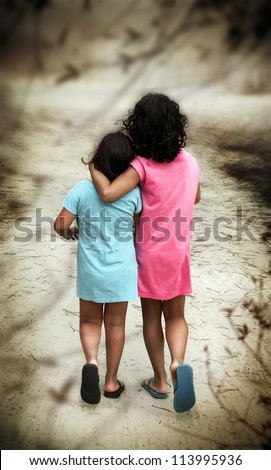 Two young girls in blue and pink dresses walking away with their backs turned - stock photo