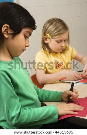 Two young girls in classroom creating art. Vertical shot. - stock photo
