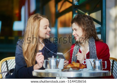 Two young girls in Parisian outdoor cafe, drinking coffee with croissant and listening music using earphones. Friendship concept