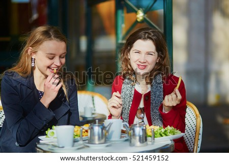 Two young girls in Parisian outdoor cafe, eating French fries. Friendship concept