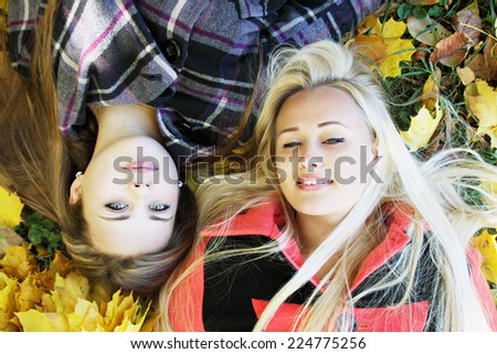 two young girls lie on the grass - stock photo
