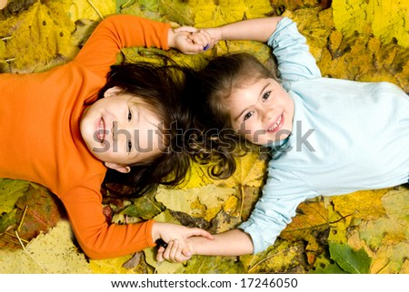 Two young girls playing in the Autumn Leaves. - stock photo