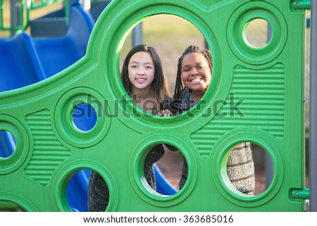 Two young girls playing together at school playground - stock photo