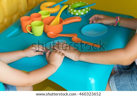 Two young girls playing with colorful plastic kitchen toys, holding hands, pretend dinner time.