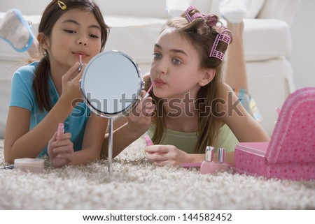 Two young girls playing with makeup - stock photo
