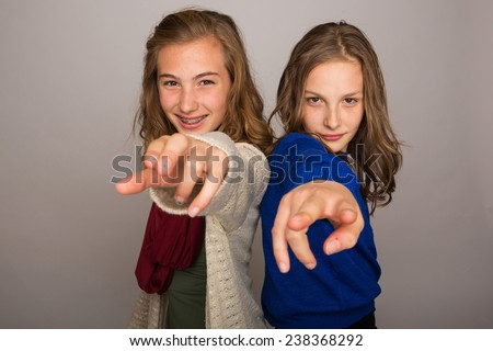 two young girls pointing their fingers at camera - stock photo