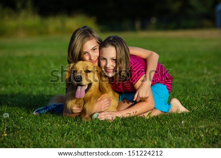 two young girls pose with a beautiful golden retriever dog - stock photo