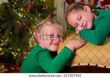 Two young girls relaxing near their christmas tree