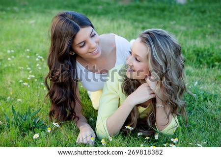 Two young girls resting on the grass. The best friends