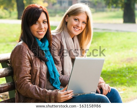Two young girls sitting in the park and using laptop,Using laptop