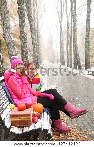 two young girls sitting on a bench covered with snow - stock photo