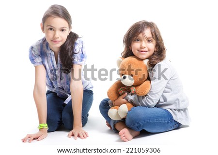 two young girls smiling sitting on the ground with a teddy bear on white background