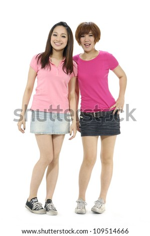 Two young girls standing isolated on white background - stock photo