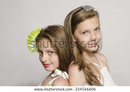 Two young girls staying back to back, sisters having fun, little sister and big sister smiling - stock photo