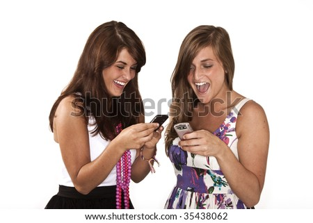 two young girls texting on their cell phones - stock photo