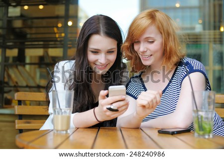 Two young girls using smart phone at the outdoors cafe  - stock photo