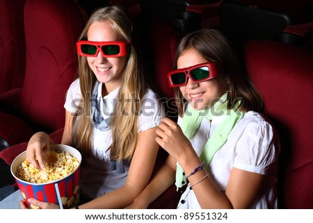 Two young girls watching movie in cinema - stock photo