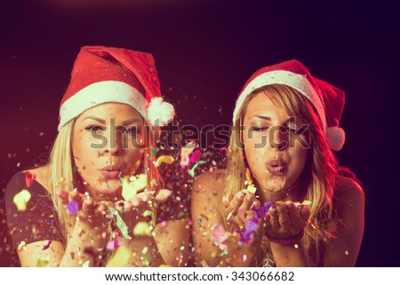 Two young girls wearing Santa's hats, blowing away colorful confetti at New Year'a Eve party - stock photo