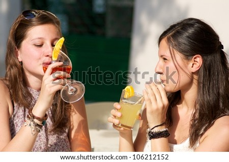 Two Young Girls While They Take a Cold Drink - stock photo