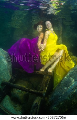 Two young graceful women in a dress posing near the stairs in the lake - stock photo